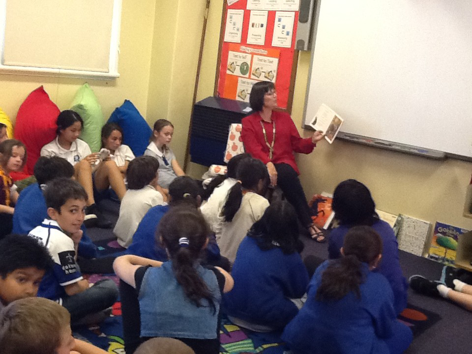 Students gathering round to hear a story in our library.